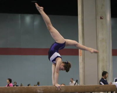 gymnast doing handstand on beam